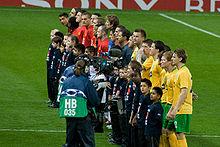 Les joueurs du Celtic (au premier plan, en jaune) et de Manchester United (en arrière-plan, en rouge) et les officiels du match (en gris) s'alignent avant le match de phase de groupes entre les deux équipes.  Chaque joueur a une mascotte d'enfant portant une chemise bleu marine debout devant lui, et une équipe de caméra de télévision se concentre sur les joueurs celtiques.