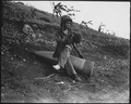 Using an unexploded 16-inch naval shell for a resting place, Marine Private First Class Raymond Hubert, shakes a... - NARA - 532530.tif