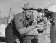 A smiling man in a short-sleeved shirt, dark pants, and a light-colored bucket hat examining a piece of mechanical equipment