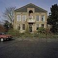 Voorgevel van pastorie met ingangspartij, balkon en loggia op de verdieping gezien vanaf de straatzijde - Hauwert - 20406561 - RCE.jpg