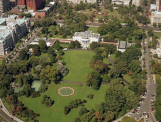 New Executive Office Building - The New Executive Office Building shown in an aerial photograph of the White House Complex and surrounding area. The NEOB is the brick building in the extreme upper left-hand corner of the photo. The White House is in the center.