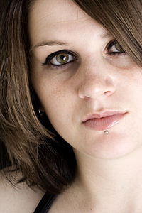 Woman with hazel eyes and labret piercing gazes at the camera.jpg
