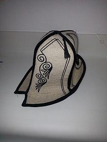 Photographie d'un chapeau de feutre blanc orné de motifs noirs.