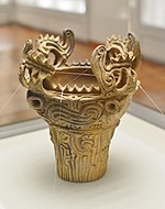 Vessel with flame-shaped ornamentation on the rim.