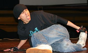 A breakdancer in the middle of a downrock.