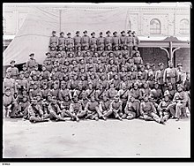 Eight rows of men in uniform with slouch hats in front of a building