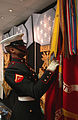 A Marine adjusts the Marine Corps flag prior to the Hall of Heroes ceremony for Jason L. Dunham.jpg