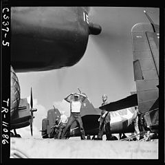 "A plane handler giving the signal, ""Lock tailwheel"", to an F6F pilot aboard the USS Tulagi (CVE-72) off the coast of... - NARA - 520859.jpg"