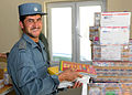Afghan National Civil Order Police Sergeant helps load boxes of school supplies to be distributed to a local school. (4677625215).jpg