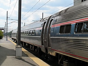 Corrugated silver tubular rail cars with red, white, and blue striping