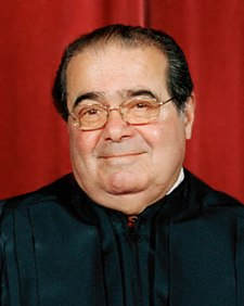 A heavyset, middle-aged balding man wears the black robes of a judge. He looks towards the camera, almost smiling.