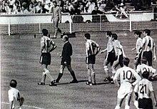 Photographie en noir et blanc. Au centre de la photographie, l'arbitre, en noir, accompagne le joueur argentin Antonio Rattín vers l'extérieur du terrain, à gauche, suivis d'autres joueurs argentins et sous l'œil de joueurs anglais et argentins au premier plan, qui tourne le dos au spectateur de la photographie.