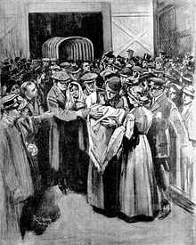 A man wearing a bowler hat and a woman in a shawl embrace among a crowd of people standing in a wooden building