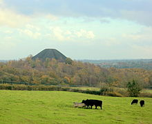 Black conical hill showing above trees and fields