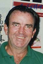 Middle-aged man wearing a green polo shirt, with brown hair combed back, smiling.