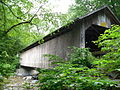 A light brown wooden covered bridge seen from one side of the river it crosses, slightly below the portal. It is surrounded by green tree branches on either side.