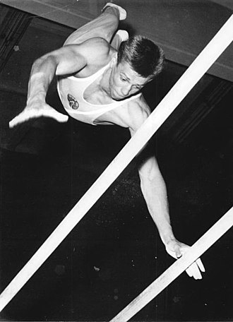Artistic gymnastics - A gymnast performing on the parallel bars in 1962.