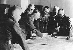 Photo noir et blanc. Dans une pièce aux murs clairs, sept officiers généraux en uniforme suivent les indications données par Adolf Hitler pointant de sa main droite un lieu sur une carte étalée devant eux sur une table. Les huit hommes sont debout autour de la table; Adolf Hitler et le général Friedrich Paulus sont au centre de la photo.