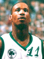 "A man, wearing white shirt with a logo and the word ""NBA PLAYERS"" on the front, is standing and posing for a photo."