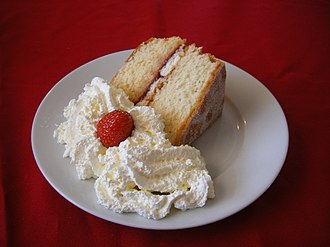 Sponge cake - A slice of Victoria sponge cake, served with cream and a strawberry