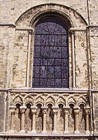 """The """"blind arcade"""" beneath this window at Canterbury Cathedral has overlapping arches forming points, a common decorative feature of Romanesque architecture in England."""