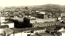 Photograph from an elevated vantage point looking over the rooftops of multistory buildings in a crowded downtown district toward a large bay with many steam and sailing ships riding at anchor and a mountain in the distance on the other side of the inlet
