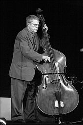 Black and white image of a man in a suit playing on a bass (a large string instrument).