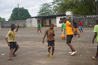 Children play football at University of Liberia basketball court.jpg