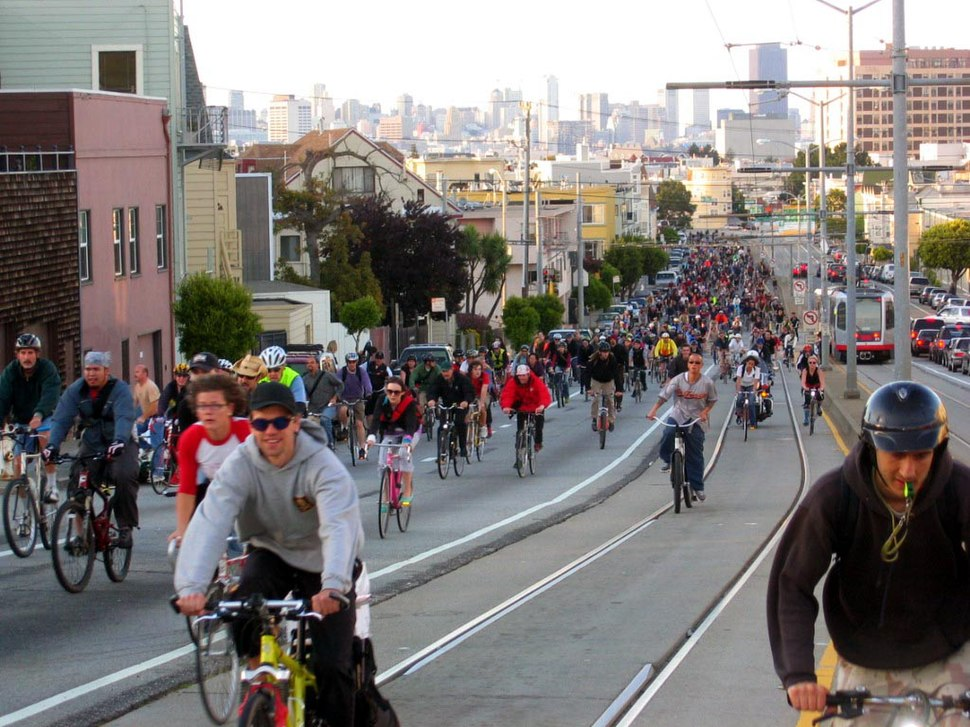 Many cyclists on a road, all going in the same direction.