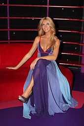 A smiling wax figure styled with blonde hair and outfitted in a blue and purple dress and heels sits cross-legged
