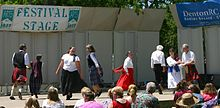 Four couples dressed in Celtic costumes dance on stage on a sunny day with audience in seats looking on.