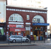 "A red-bricked building with a white sign reading ""EDGWARE ROAD STATION"" in red letters with a car driving in the foreground"