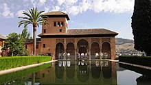 A Moorish style palace with a pool and a garden.