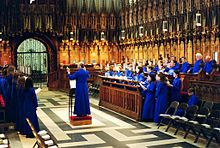 A view in the choir of York Minster with girl choristers and male lay clerks in blue cassocks standing in the richly carved choir stalls.