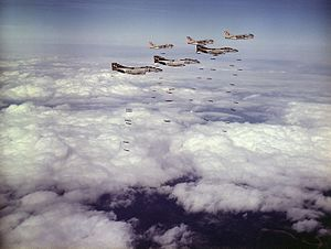 F-4B Phantoms of VF-161 and A-7C Corsairs of VA-86 drop bombs on Vietnam in March 1973.jpg