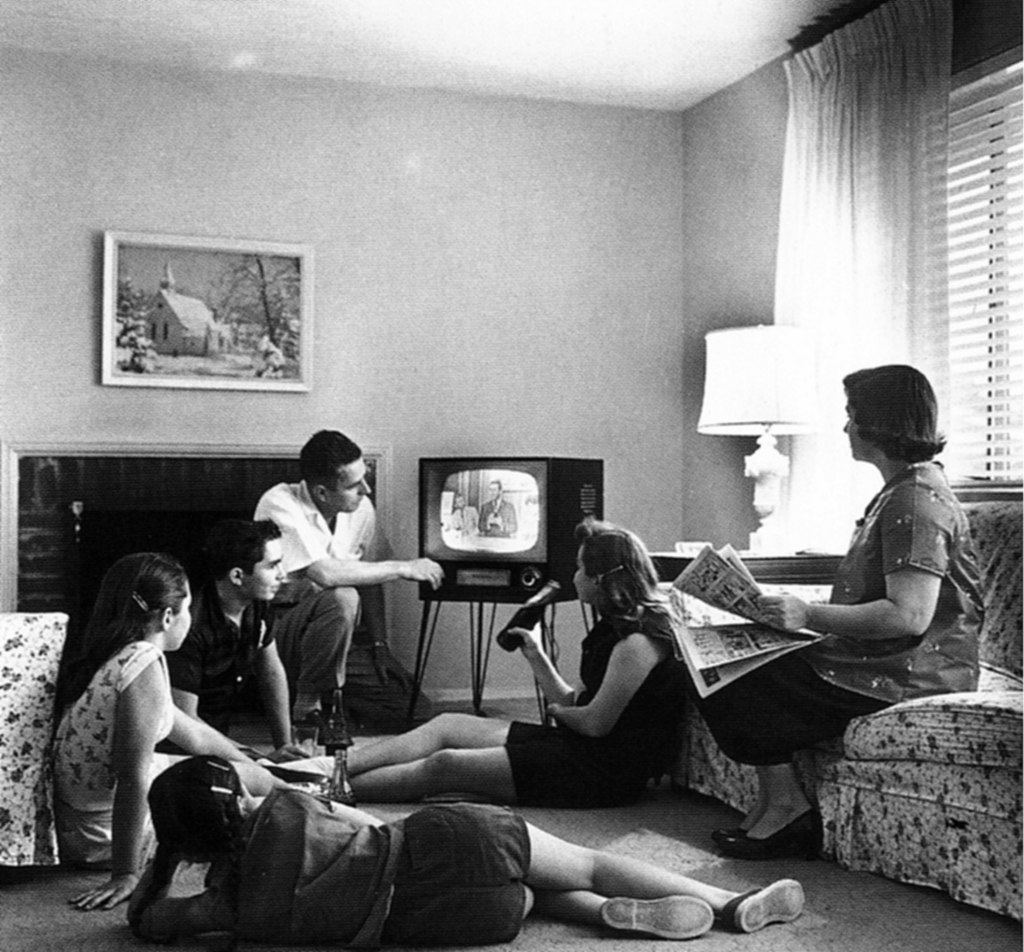 A family grouped around a television set.