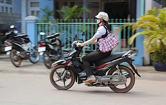 Human skin color - A Vietnamese motorcyclist wears long gloves to block the sun, despite the tropical heat.