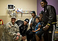 Football players with the 2014 U.S. Army All-American Bowl teams, along with their mentor, U.S. Army Sgt. 1st Class Joseph Kishel, left, assigned to the 5th Recruiting Brigade, pose for a photo with a child 140101-A-JW984-048.jpg