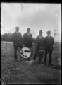 Four men standing behind a three position ground signal at Trentham. ATLIB 289015.png