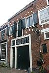 foto van Pand met rechte kroonlijst, ontlastingsbogen met blokken versierd boven de vensters, thans pakhuis