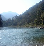 Hanging bridge over a river lined with tropical vegetation in a mountainous landscape.