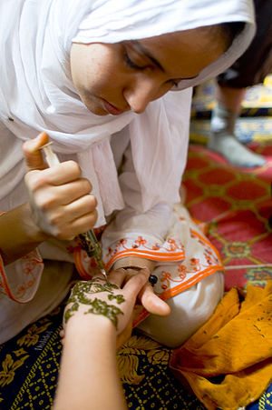 Girl putting henna in hands. Morocco.