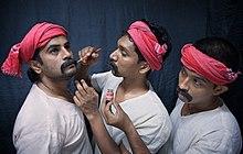 """""""Photographie de trois acteurs, dont l'un maquille le visage d'un autre."""""""