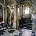 Interieur, overzicht van het trappenhuis aan de smalle zijde van de hoofdentree, met zuilen, gewelf en tegelvloer - 's-Gravenhage - 20387428 - RCE.jpg