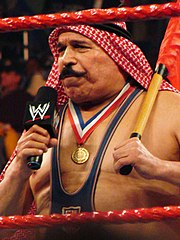 Behind two red ropes stands a man with a large mustache speaking into a microphone and holding a flag.