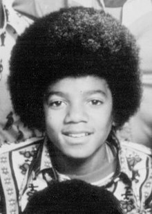 Black & white photo of Jackson as a chubby-cheeked teenager with afro hairstyle. He has a wide nose.