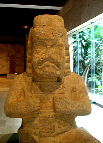 Werejaguar - A stone Olmec were-jaguar, showing common were-jaguar characteristics including a downturned mouth, almond-shaped eyes, pleated ear bars, a headdress with headband, and a crossed-bars icon on the chest