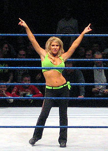 A blond woman poses in a wrestling ring with blue ropes. Her arms are outstretched, and she is pointing to either side. She is wearing a green crop top, with a matching green belt, and black trousers.