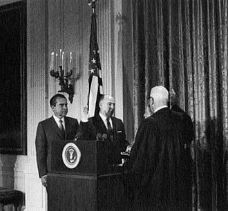 John N. Mitchell - Mitchell is sworn in as Attorney General of the United States, January 22, 1969. Chief Justice Earl Warren administers the oath while President Richard Nixon looks on.