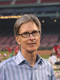 A portrait shot of a merry-looking middle-aged Caucasian male (John W. Henry) looking straight ahead. He has short greying hair, and is wearing a blue-striped shirt with the top button open. In the background is a baseball stadium.